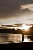 Man walking by still lake - Stock Image - CNNFGA