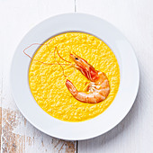 Carrot soup with shrimp on white wooden background - Stock Image - DDCPEW