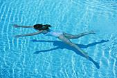 Woman swimming in pool - Stock Image - BJK1GF