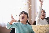 Playful girls throwing popcorn - Stock Image - CBT654