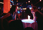 Young man and woman sitting in bar, talking at table, dramatic lighting. - Stock Image - AWMY3D