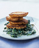 Salmon cakes on spinach - Stock Image - BD5171
