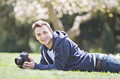 Man laying with camera in park - Stock Image - DKPG03