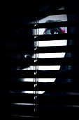 A partially hidden face of a young woman behind a screen - Stock Image - BDPMR1