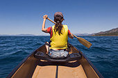 Rear view of woman paddling canoe - Stock Image - BAXF8Y