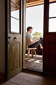 Man reading on porch - Stock Image - CNTF4P