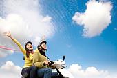 Happy young couple having fun on a scooter - Stock Image - CBNMNA