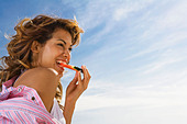 Woman with smile eats watermelon outside. - Stock Image - AM9KKG