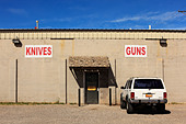Shop selling knives and guns, New Mexico, USA (vehicle license obscured). - Stock Image - CCC4GW