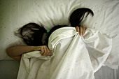 Five year old girl hides beneath sheets after tantrum - Stock Image - B2E1F5