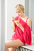 young woman eating grapefruit - Stock Image - BC729W