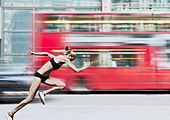 Athlete racing bus on city street - Stock Image - C84C1N