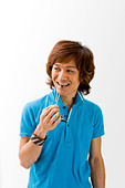 Smiling Asian guy in blue t shirt holding sunglasses and biting on it isolated - Stock Image - B35G3B