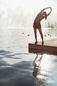 Woman stretching by still lake - Stock Image - CNMRYH