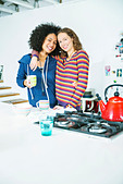 Women hugging in kitchen - Stock Image - DAM1Y9