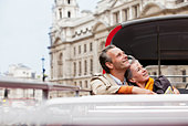 Smiling couple looking up on double decker bus in London - Stock Image - CC9G8E