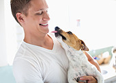 Smiling man holding dog - Stock Image - D7Y6N7