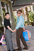 Gay couple window-shopping - Stock Image - AHNCBX