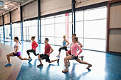 Group of people doing lunges in fitness class - Stock Image - DA72R8