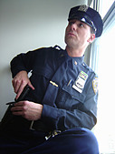 Portrait of a New York City Police Officer Near a Window He is Touching His Gun - Stock Image - AT6ATT