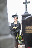 Germany, Bavaria, Young woman with flower at graveyard - Stock Image - C3R3G7