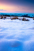 Snow fields on Black Mountain with views towards Carreg Cennen and Towy Valley Carmarthenshire Wales at sunset - Stock Image - BNHKY4