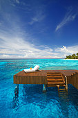 Sun lounger and jetty in blue lagoon on tropical island, Maldives, Indian Ocean, Asia - Stock Image - CFR9HW