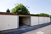 One open garage in row - Stock Image - CN3A12