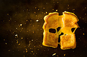 A Grilled Cheese Sandwich cut in four squares pulling the cheese on a wood table - Stock Image - C088JK