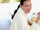 Woman in robe eating healthy breakfast outdoors - Stock Image - ACCBRR