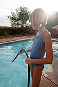Ten year old girl pouring water into a swimming pool from a hose. - Stock Image - D3E6AJ