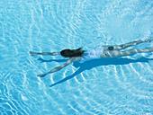 Woman swimming in pool - Stock Image - BJK1G4