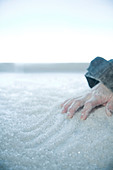 frozen hand lying on snow and ice. exterior location, - Stock Image - BX77W6