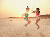 Girls jumping rope on beach - Stock Image - DXKRNC