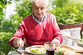 Senior man having lunch outdoors - Stock Image - EA09MK