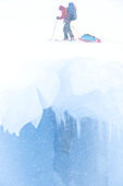 A skier tows a toboggan over an open crevasse in the Darwin Range of southern Chile - Stock Image - CFC2XH