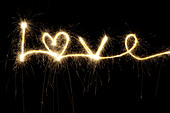 LOVE written with a sparkler at night including a heart shape - Stock Image - CBX80B