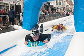 Isle of Wight, UK. 12th July, 2015. Bestival waterslide down Ryde high street on the Isle of Wight. The event will see around 300 people slide down a 200m inflatable waterslide on lilos. 12 July 2015. © Rob Wilkinson/Alamy Live News - Stock Image - EXDK83