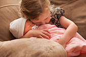 USA,Utah,Lehi,Girl (2-3) embracing baby sister on sofa - Stock Image - C4WT0F