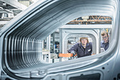 Apprentices inspecting car in factory - Stock Image - D2AHWJ