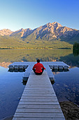 Middle age male meditating on dock at Pyramid Lake, Jasper National Park, Alberta, Canada. - Stock Image - CFBXMN