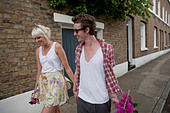 Couple walking home from flower market in summer, london, england, uk, europe - Stock Image - BJ8RYM