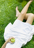 Woman lying in grass, holding apple, low section - Stock Image - A5T24K