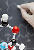 Molecule model with researcher writing on blackboard in the background - Stock Image - CFD0DX