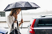 Businesswoman talking on smart phone during rainy season in city - Stock Image - ECKTG1