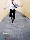 Businessman Playing Hopscotch - Stock Image - EEJRTH