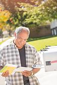 Man retrieving mail at mailbox - Stock Image - E3MNWT