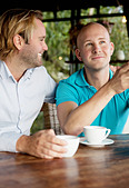 Two gay men sitting by table - Stock Image - BKWE4T