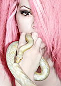 Portrait of a young woman with pink hair and an albino snow corn snake - Stock Image - BXYHJ2