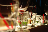 Still Life of Many Beverage Glasses on a Bottom Lit Shelf after a Party - Stock Image - AJXMMH